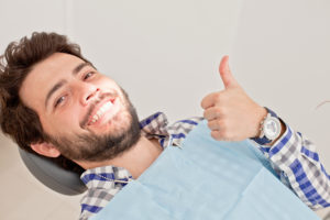 man smiling while seated in dentist chair