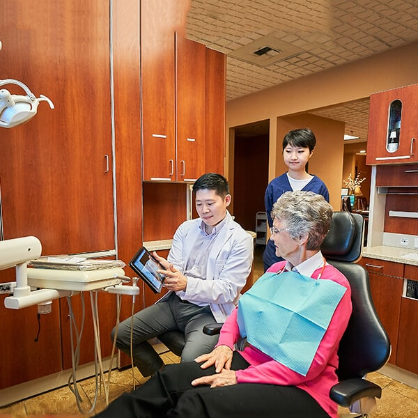 Dr. Hu talking with a female patient about dental care while using a tablet.