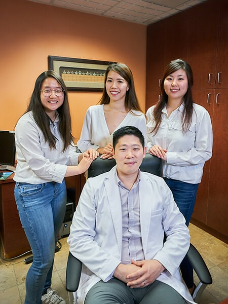 Dr. Hu sitting in his chair with his three assistants standing behind him and smiling