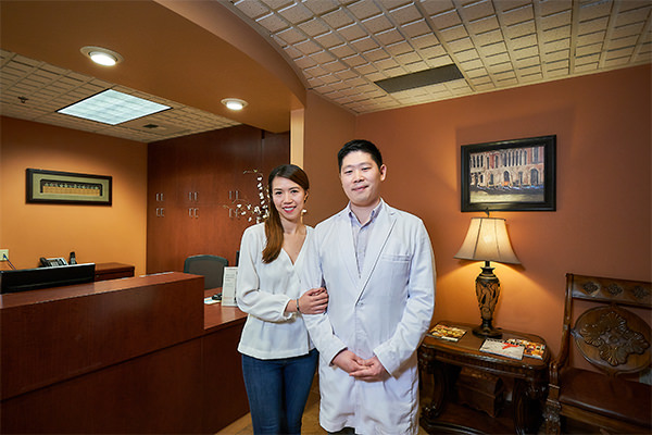 Our Renton dentist wearing his dental coat and smiling with his wife