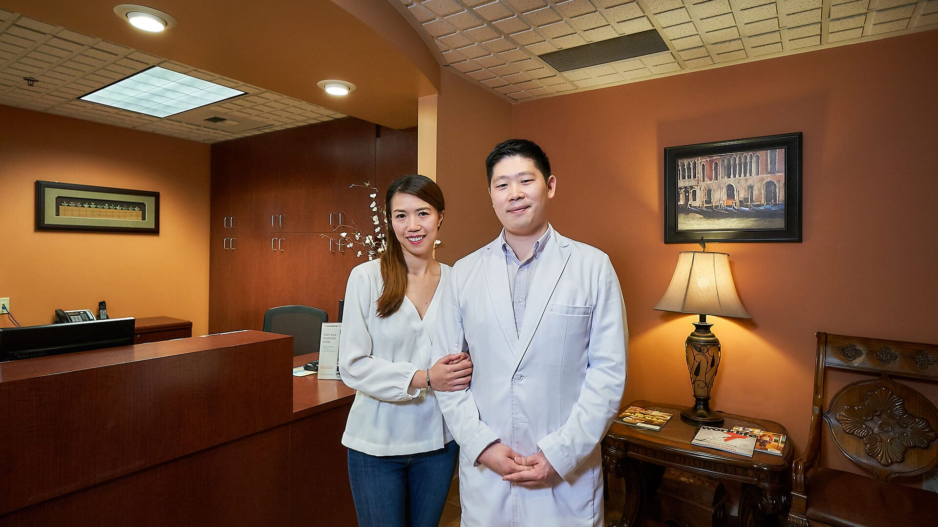 Dr. Hu with his wife inside the dental office hugging each other