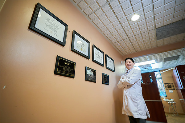 Dr. Yuchen hall standing with his arms folded next to his wall of certificates