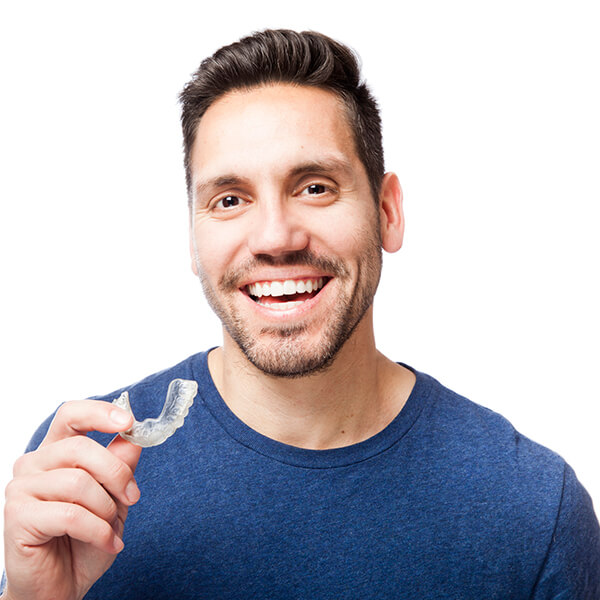 A man in a blue shirt holding some Invisalign aligners in his hand