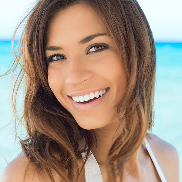 A young woman smiling at the beach