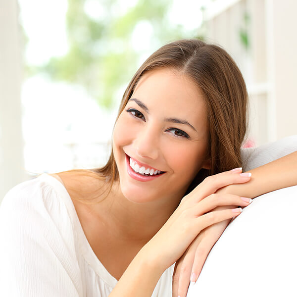 A young brown-haired woman smiling while sitting on a sofa with a bright white smile thanks to teeth whitening.