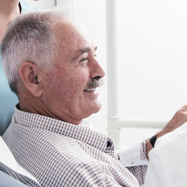 A side profile of a male patient sat in the dentist's chair
