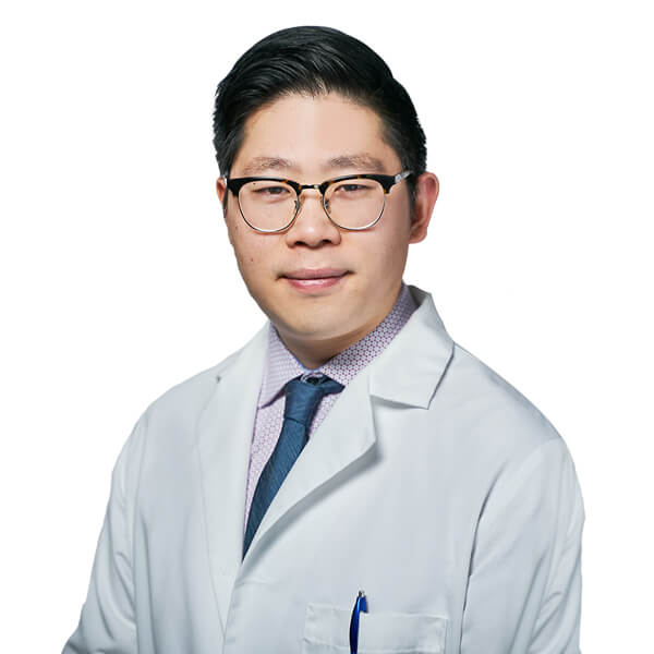 Dr. Yuchen Hu, a Renton dentist looking straight ahead while wearing his dentist uniform and glasses