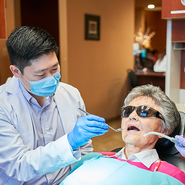 Dr. Hu checking the teeth of an elderly female patient in our office