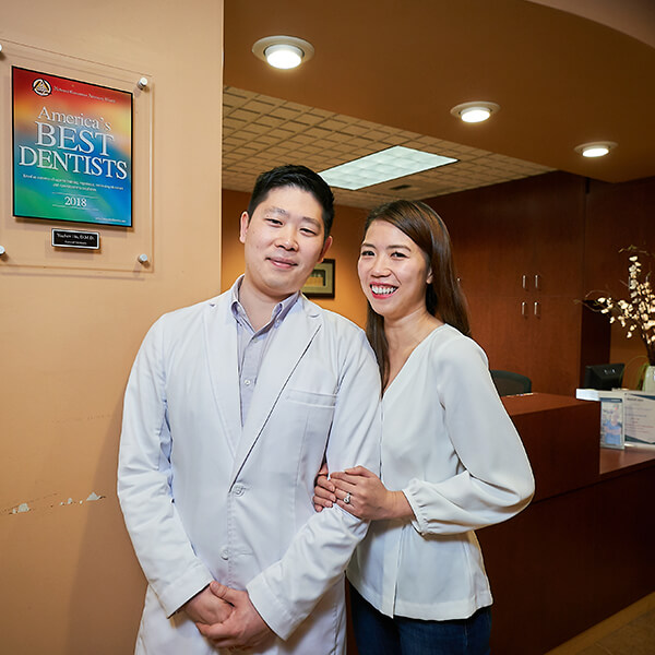 Dr. Hu and his wife smiling while standing next to his award