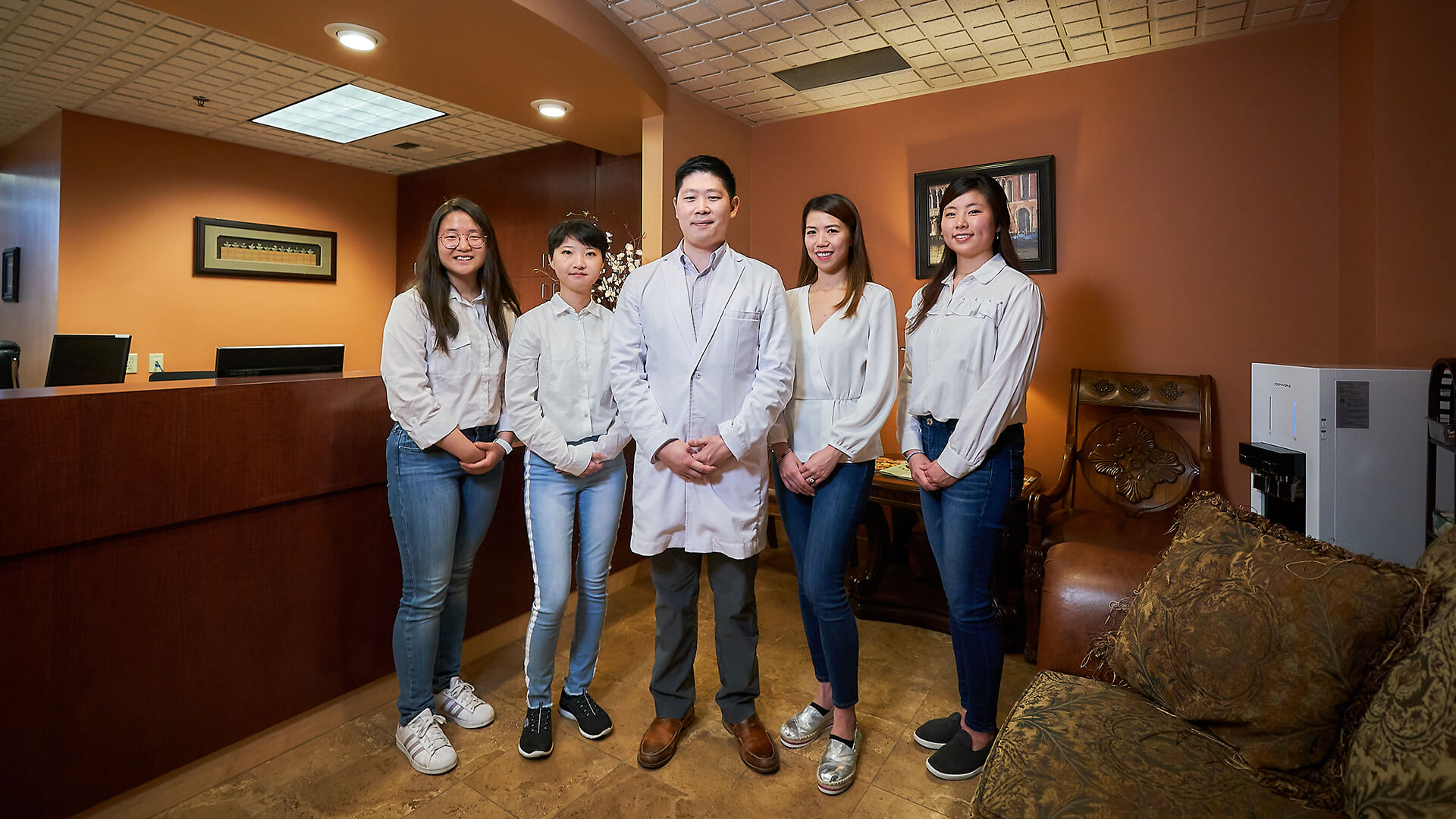 Dr. Hu and his four female dental assistants smiling inside the dental office