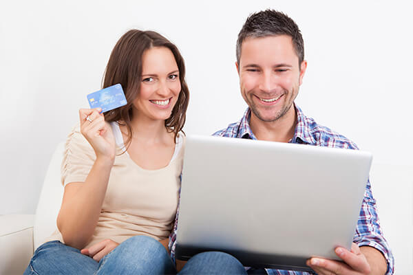 A man and a woman looking at dentistry on their laptop and paying with a credit card