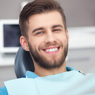 A young man with a short hair sitting in the dentist's chair and having family dentistry