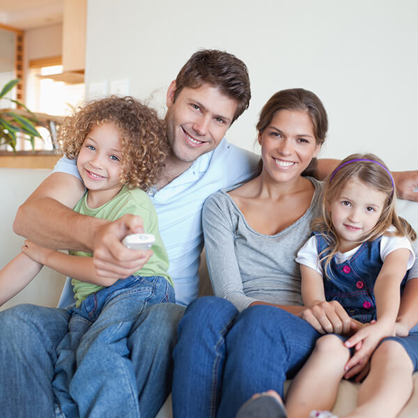 A family of four smiling and hugging while sitting on a sofa with healthy smiles thanks to our Renton dentistry