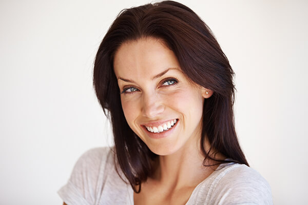 A dark haired woman smiling and folding her arms