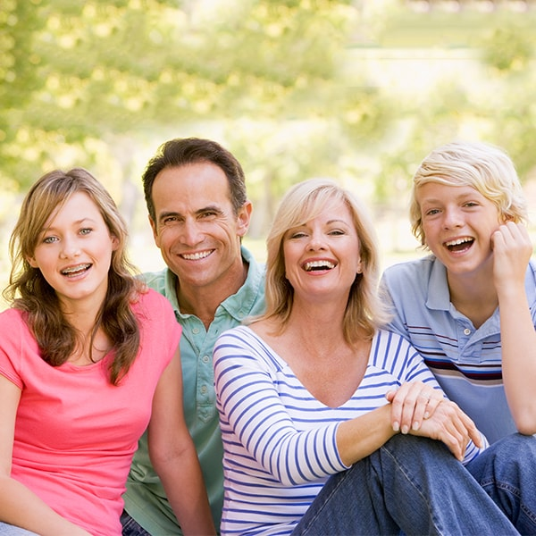 A family of four smiling in the park because they are happy and healthy thanks to our family dentistry in Renton, WA