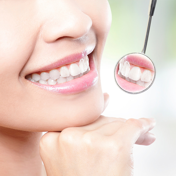 The close-up smile of a young woman with pink lipstick holding her hand under her jaw while reflecting her teeth in a small circular mirror
