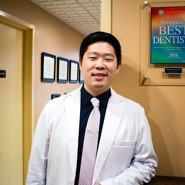 Dr. Hu inside Hu Smiles In Renton's dental office smiling while wearing a striped tie, and his dentist uniform