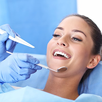 Close-up of woman being checked by the dentist using a dental instruments