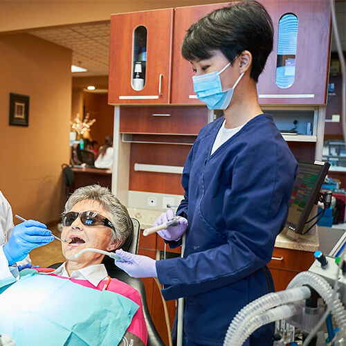 Our hygienist performing an examination on an elderly patient inside the Hu Smiles dental office