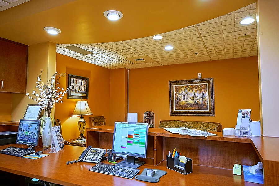 The Hu Smiles in Renton dental office showing our receptionist's desk with two computers, some pens and flower vases